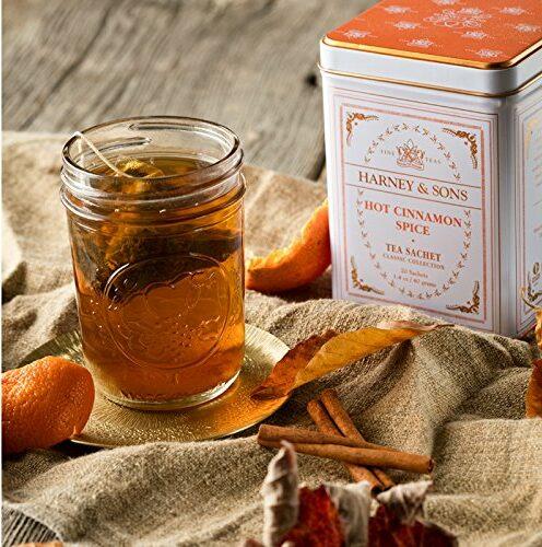 tin of hot cinnamon spice tea sachets from harney and sons with mason jar of tea on burlap cloth with garnish