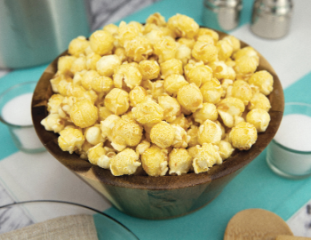 bowl of kettle corn popcorn with little ramekins of salt all on blue tablecloth with kitchen supplies
